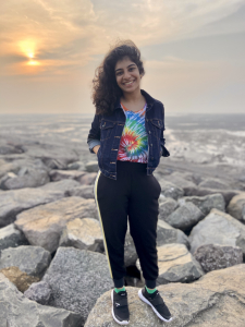 Young Indian woman in a tie-die t-shirt, tracksuit bottoms, green socks, trainers and a denim jacket. Standing on some rocks in front of a sunset.